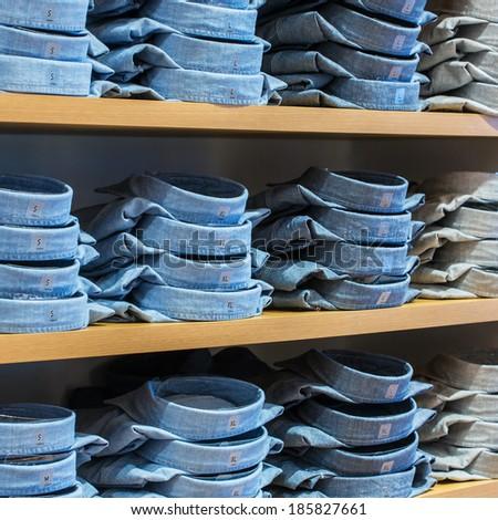 Neat stacks of folded clothing on the shop shelves - stock photo