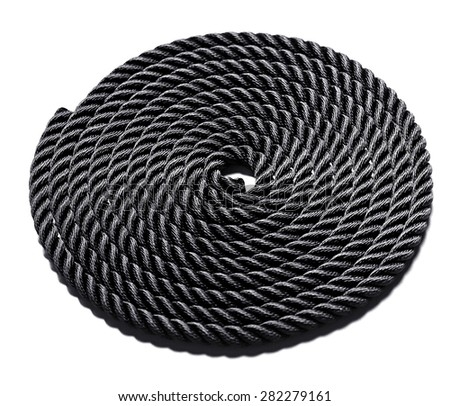 Neatly coiled black rope forming a perfect circle and showing the texture of the interwoven and braided fibers isolated on white - stock photo