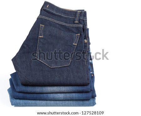 Neatly folded blue denim jeans with the pocket and stitching visible displayed on white - stock photo