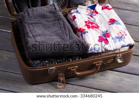 Neatly stacked men's clothing. Shirt and trousers in the suitcase. - stock photo
