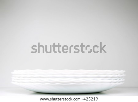neatly stacked plates - stock photo