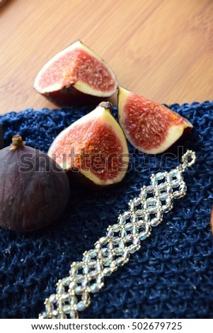 Necklace and fig fruit fashion composition on the wool scarf for autumn season