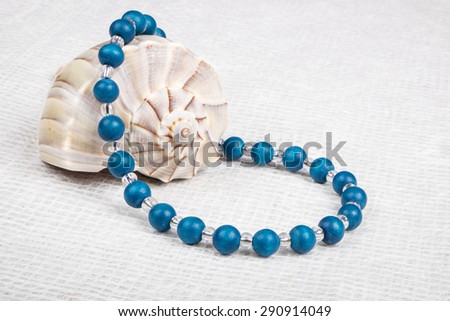 Necklace Made with Blue Wood Beads Displayed Over a Lightning Whelk Shell - stock photo