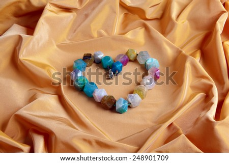 necklace of gems heart shaped on orange background - stock photo