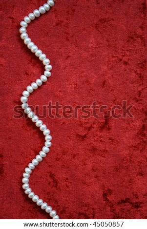 Necklace of white pearls on a terracotta velvet as background