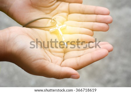 Necklace with a cross in hand - stock photo
