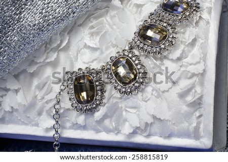 necklace with precious stones on the texture of the flowers - stock photo