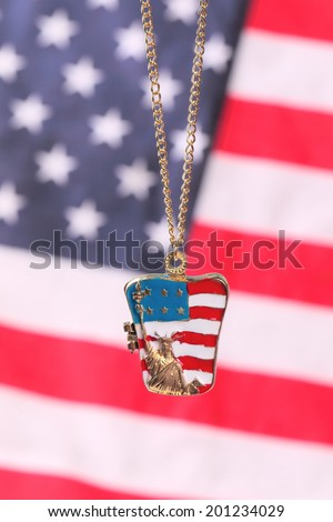 Necklace with statue of liberty on the american flag background - stock photo