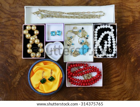necklaces, rings, earrings, pearls and gold in boxes on a wooden background - stock photo
