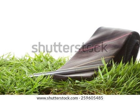 Necktie and chrome pen put on the green grass as a background represent the accessory of formal business uniform. - stock photo