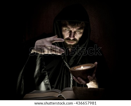necromancer casts spells from thick ancient book by candlelight on a dark background - stock photo