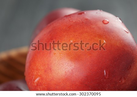 nectarines in olive wood bowl on oak table, shallow focus