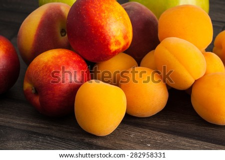 Nectarines, Peach and apricots on wooden table - stock photo