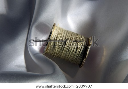 Needle and Thread on a spool on cloth - stock photo