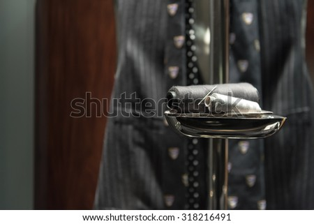 Needle and Thread on Stand with Suit Waistcoat and Tie in Background - stock photo