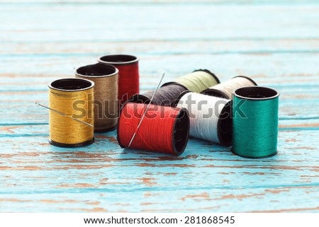 needle colorful thread needlework embroidery tailor craft repair background blue wood teak still life vintage - stock photo
