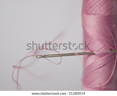 Needle in the pink bobbin - stock photo