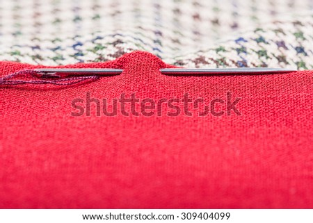 needle sews two pieces of cloth close up - stock photo