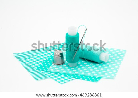 Needle, thimble, thread, colored pieces of cloth isolated on white background