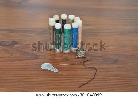 Needle, thread and threader - stock photo