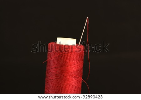 needle with a red thread on a black background - stock photo