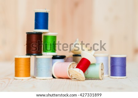 Needles, thread, scissors on wooden background.