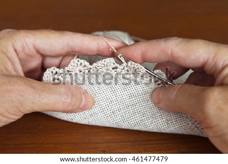 Needlework. Female hands crochet linen doily