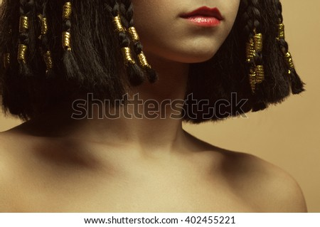 Nefertiti - queen consort of Egypt concept. Portrait of beautiful young brunette with natural hairstyle, perfect make-up, posing over beige background. Healthy hair. Close up. Studio shot - stock photo