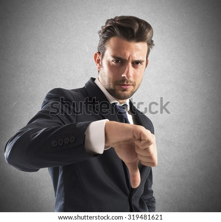 Negative mood businessman with a thumb down - stock photo