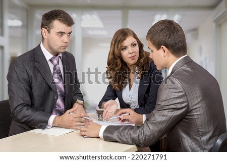 Negotiating the deal. Three business people discuss the deal. One female, two male, business dress code, - stock photo