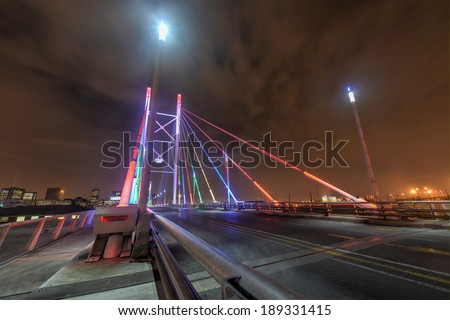 Nelson Mandela Bridge at night. The 284 meter long Nelson Mandela Bridge, officially opened by Nelson Mandela himself, which crosses over the 40 railway lines that lie spread beneath its span. - stock photo
