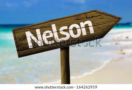 Nelson, New Zealand wooden sign with a beach on background  - stock photo