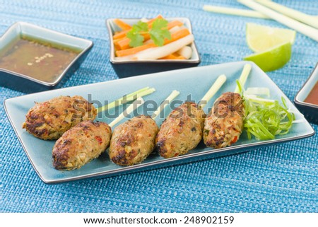 Nem Nuong Xa - Vietnamese minced pork sausages on lemongrass skewers served do chua, nouc cham and chili sauce. - stock photo