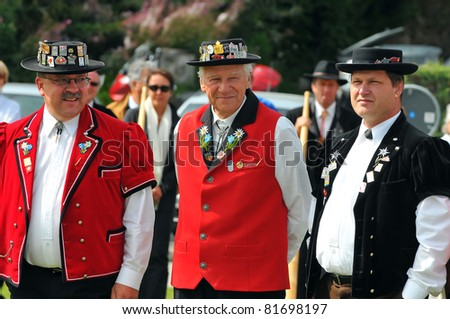 NENDAZ, SWITZERLAND - JULY 24:competition judges in traditional dress at the prize giving of  the 10th International Festival of Alpine horns :  July 24, 2011 in Nendaz Switzerland