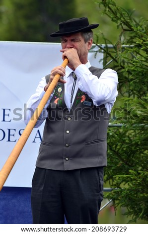 NENDAZ, SWITZERLAND - JULY 27: Thomas STOFER solo at the  finals of the 13th International Festival of Alpine horns :  July 27, 2014 in Nendaz Switzerland