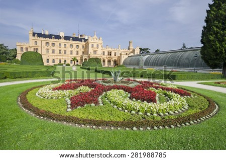 Neogothic Lednice chateau with flowering garden and greenhouse, Czech republic - stock photo