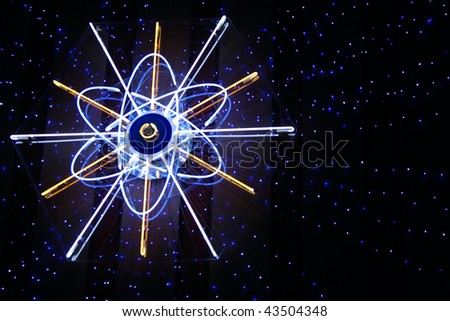 Neon atom sign on the wall with beaming blue small stars around.