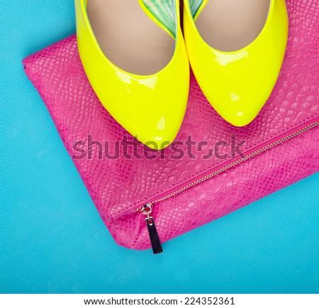 Neon high heels and snakeskin print bag, woman fashion concept - stock photo