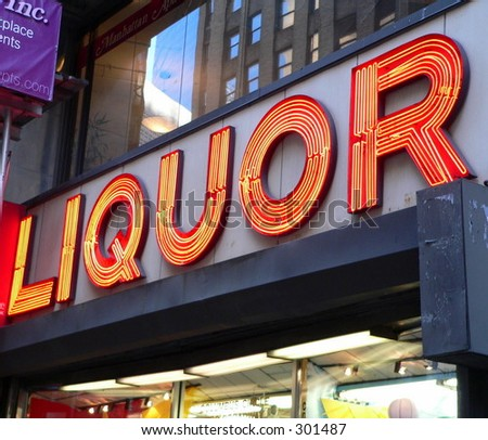Neon Liquor sign in front of Store - stock photo