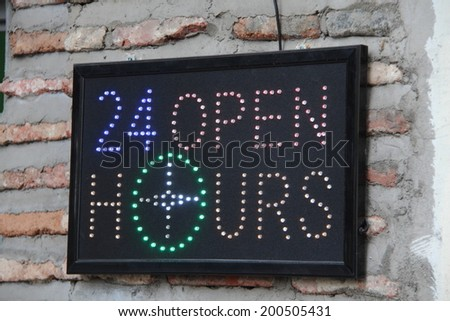 Neon Open Sign 24 hours on wall background - stock photo