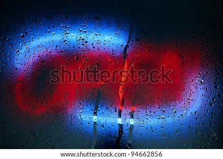 Neon open sign illuminates a foggy, rain covered window - stock photo