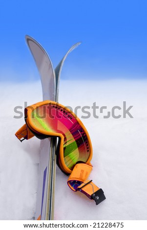 Neon Orange Ski Goggles in Snow with Skis - stock photo
