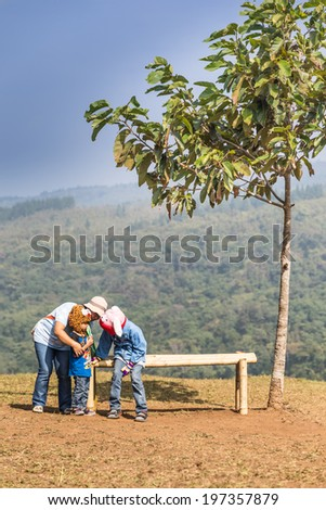 Neon Phoem,Phitsanulok,Thailand - December 29 : a family of unidentified people is enjoying on the bench in Phu Hin Rong Kla National Park,Phitsanilok,Thailand on 29 December 2013 - stock photo