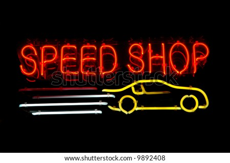 Neon sign advertising a speed shop with a racing car - stock photo