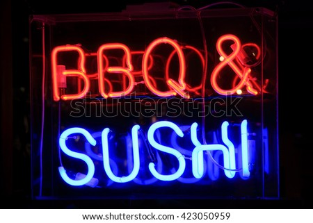 Neon sign at night advertising sushi and barbecue meals