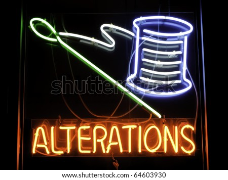 Neon sign depicting needle and spool of thread in window of dry cleaners - stock photo