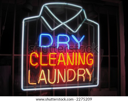Neon sign in dry cleaner's window - stock photo