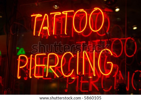 Neon sign in the window of a tattoo parlor in New York City - stock photo