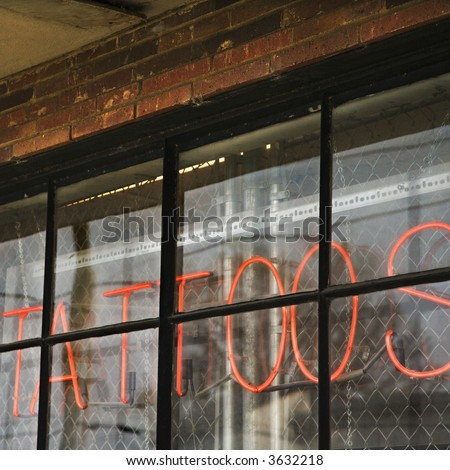 Neon sign in window for tattoos and body piercing. - stock photo