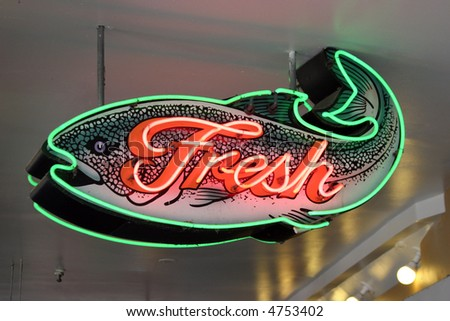 """neon sign series """"fresh"""" fish sign in green and pink neon - stock photo"""